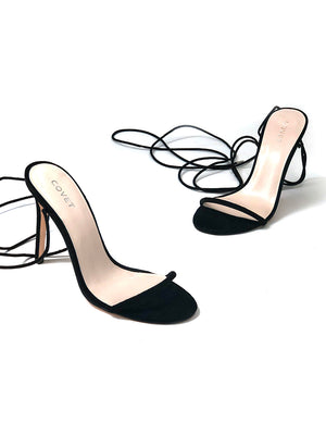Pair of black lace up heels with a stiletto heel with laces undone