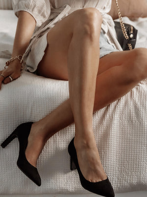 Pointed Black Pumps worn by a women sitting on a bed dressed fashionably
