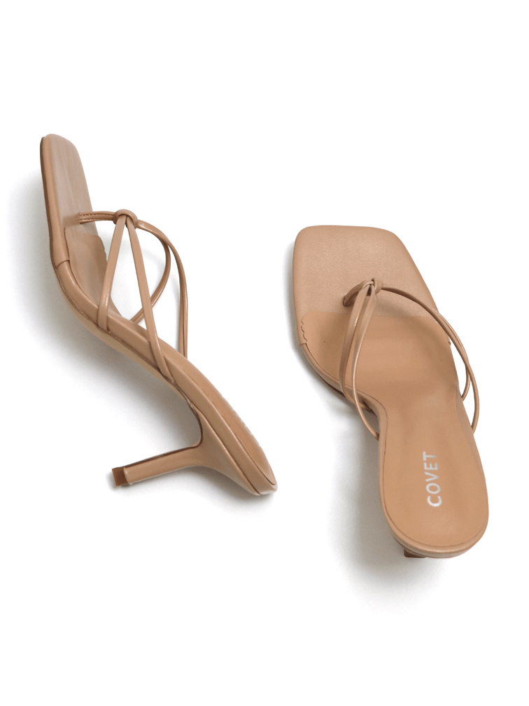 Birds eye view of a pair of nude thong stiletto sandal heels