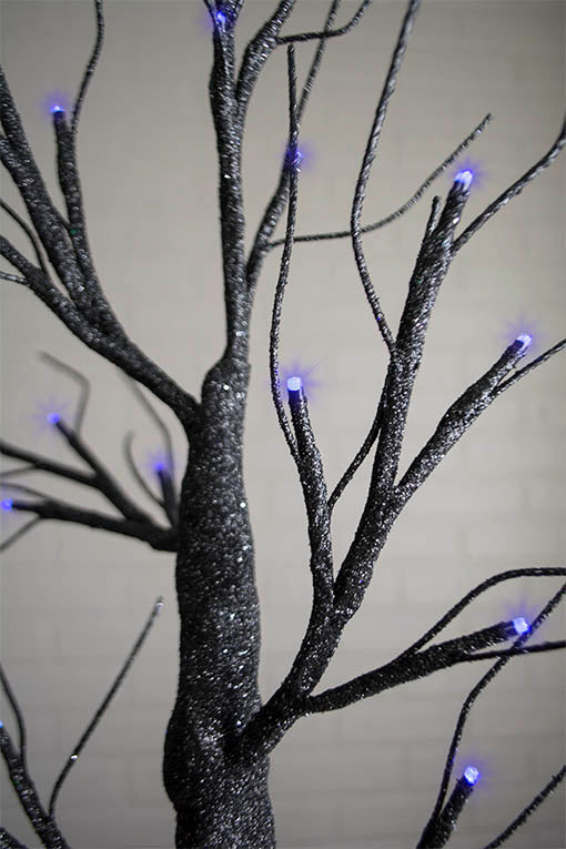 Eerie black light is cast by the deep indigo LED lights scattered throughout this creepily glittering tree!