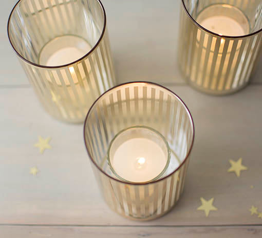 Glass-filled wax votive candles are a wonderful way to set candles into deeper holders, such as the gold tone votive shelter shown here, sold separately.