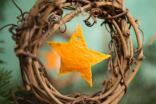 Easily create these scented ornaments using only a handful of supplies: our grapevine napkin wreath, a few strands of ribbon or twine, and the rind from small citrus fruits, such as clementines or mandarins (you could use lemons or limes as well, for more color!).