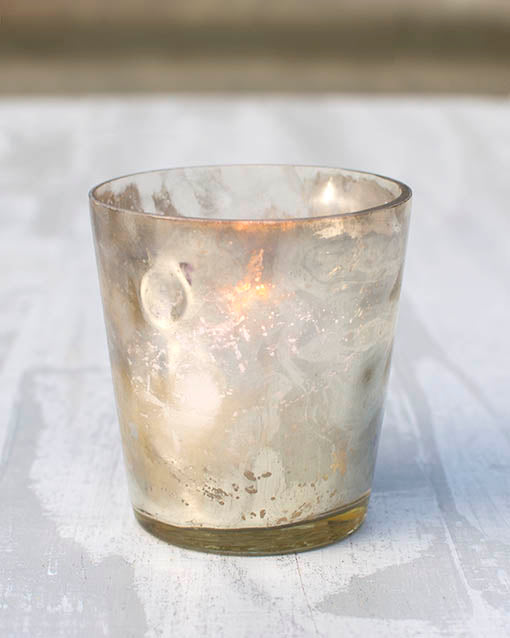The beautiful hammered texture allows candlelight to dance and shimmer through the glass of our gold votive holder.