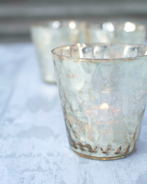 Cast dancing light on your tabletop through the hammered texture of our gold votive candle holders!