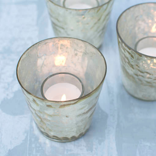 Choose real wax votives, like the wax-filled glass votives shown here, or select one of our flameless votives to make your glass votive shelter spring to life.