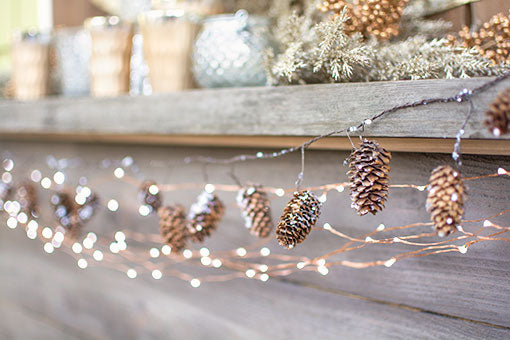 Embellish your fireplace mantel with the whimsical nature of our pine cone garland and copper wire fairy lights. Finish the look with carved bud vases, mercury glass candle holders and a sparkling sprig.