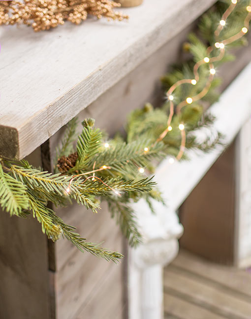 Add a faux fir garland and copper wire fairy lights to your fireplace mantel for an enchanting winter design.
