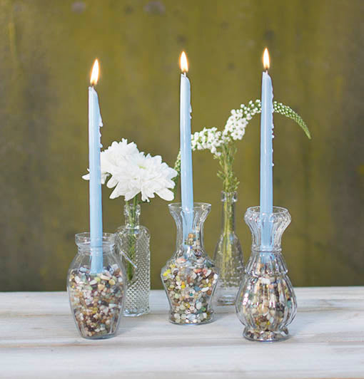 Small glass vases are the perfect showcase for your filler, supporting charming tiny taper candles at your shower, reception or birthday.