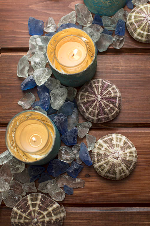 Natural sea urchin plays first mate to our sea-kissed beach glass. Perfectly paired with teal mercury glass shelters and glowing votives, your simple tablescape is awash in nautical charm.