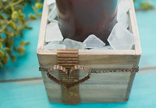 Add rustic industrial notes to your candle centerpieces using our weathered wood boxes festooned with corrugated metal ribbon decorations and filled with frosted glass fragments. All items sold separately.