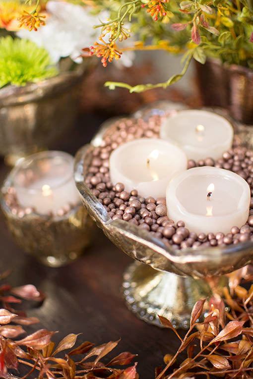Shining elegantly over gold and rich copper accents, candles arranged in our metallic clay filler bring depth to your tables and events.