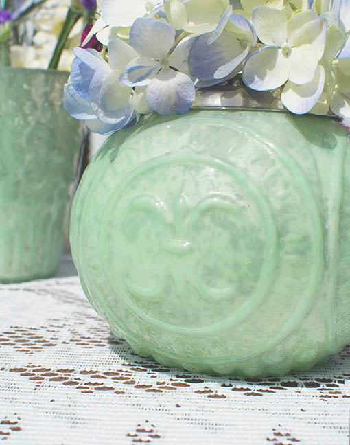 The delicate raised relief pattern on our mint mercury glass vessels is reminiscent of stately fleur-de-lis, lending itself to romantic French countryside or chic Parisian style events.