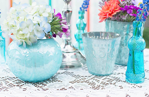 Use the full collection of pastel blue mercury glass, accented with small vintage glass bottles, to add dimension to your fashionable table.