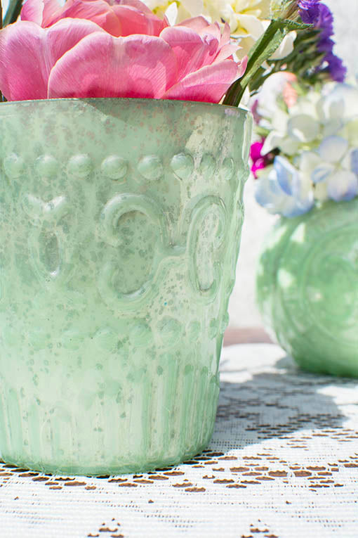 Floral petals and white lace add to the elegant vintage design of the minty mercury glass.
