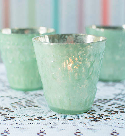 A delicate scroll relief pattern adds subtle accent to your mint-tinted mercury glass candle holder. Use any of our tea light or votive candles to cast lovely light at your event!