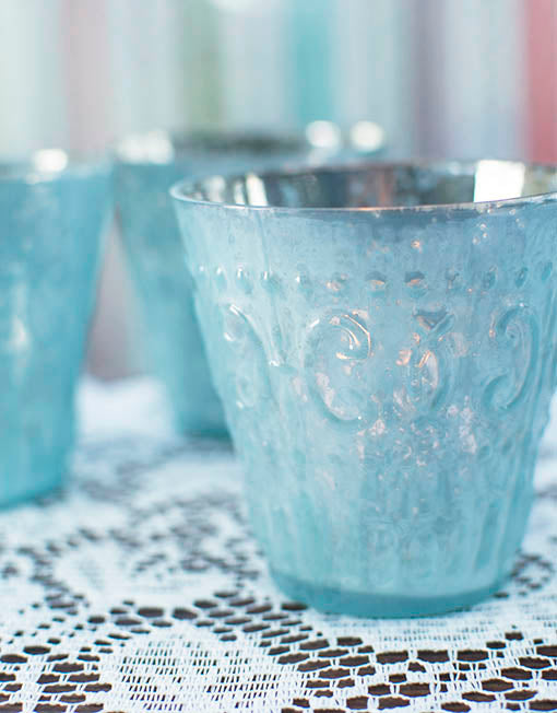 The soft relief pattern adorning these votive holders is gorgeously accentuated by candle light bouncing off its mercury glass interior.