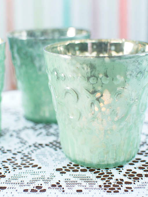 Accented with a raised pattern reminiscent of fleur de lis, our mint green mercury glass candle holders are absolument parfait for your French countryside or Parisian style wedding or party.