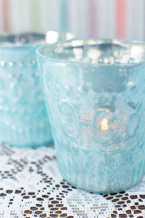 Cast a distinguished glow through the decorative relief patterns embellishing our pastel mercury glass vessels. Votive candles are available in real wax or flameless.