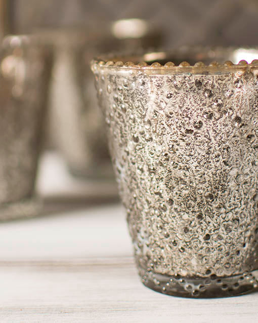 The criss-cross raised beaded pattern on the surface of our pewter mercury glass votive holders adds texture to both the light and to your table.