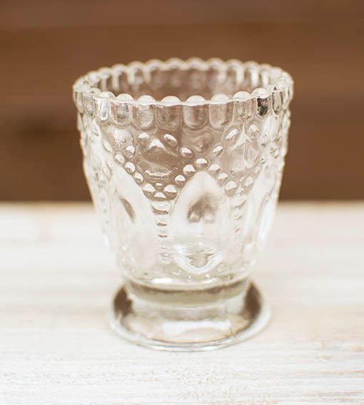 Each clear glass footed candle holder is detailed with embossed patterns and hobnail detail.