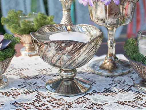 For a dramatic look, use floating candles in our mercury glass vessels, mixing and matching with abundant florals.