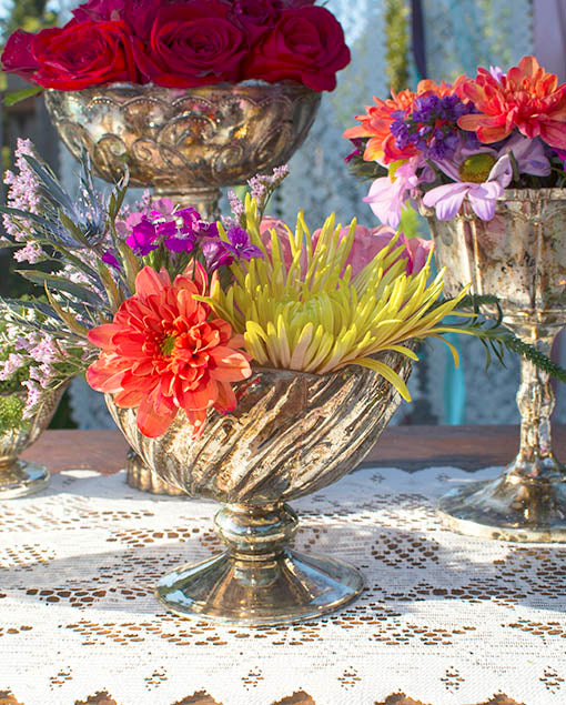 Bowlsful of blossoms are the way to dress an extravagant table! Combine jewel tone flowers and mercury glass vases and candle holders for high drama.