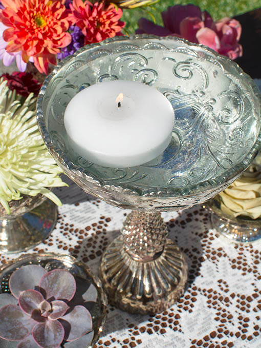 Put a spin on your centerpiece with floating candles, lace, jewel-tone florals and succulents.