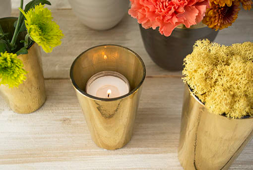 Our golden glass candle shelters are pictured with tea light candles and moss, sold separately.