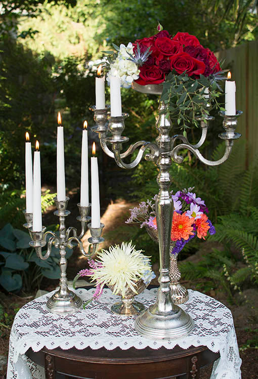 A romantic tablescape comes together with just a few easy pieces: silver tone candle ware, vintage-inspired mercury glass and freshly cut garden flowers.