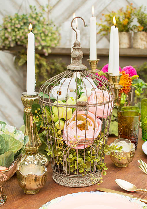 Fill our stylish tapered metal birdcage with ever blooming faux blossoms and greens and surround with luxurious gold tone table decor. All items sold separately.