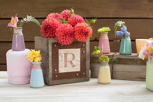 Mixing our soft-hued bud vases--necks wrapped in colorful twine--with pastel colored hobnail and rustic wood decor for a charmingly natural match. Use our corrugated metal ribbon to add stylish accents to planters that act as risers for bud vases and votive holders!
