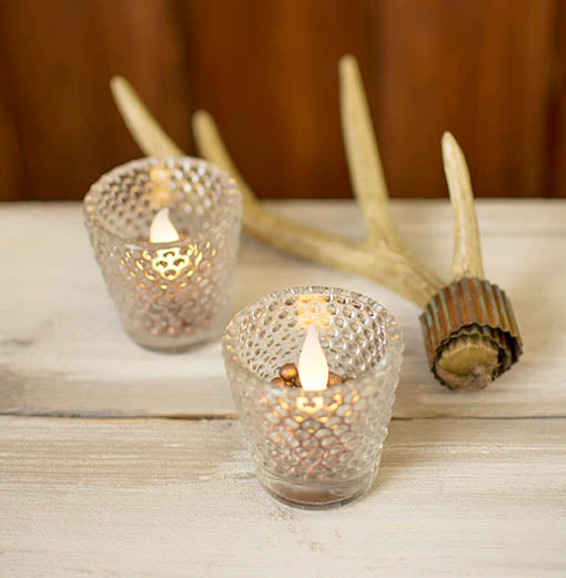 Hobnail votive holders filled with fine filler along side our antler wrapped with metal ribbon create a table scene full of rustic charm.