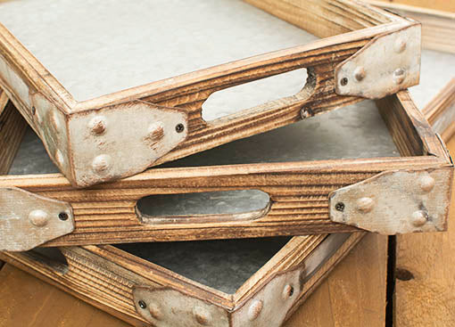 Each wooden serving tray shows off a natural grain detail encased by vintage inspired metal brackets.