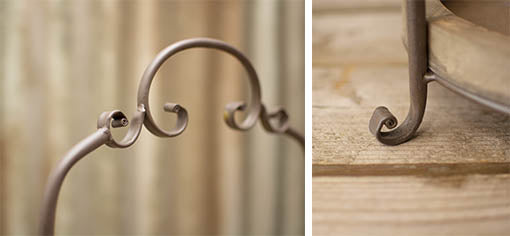 The metal frame is detailed with curling accents for a unique centerpiece.