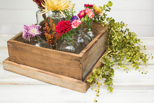 Fill this reclaimed wood pie box with vases and flowers, surrounding with sprigs and sprays as a finishing touch.