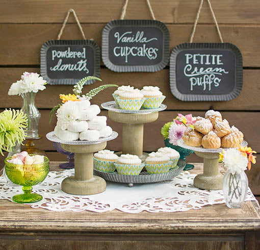 Glass plates atop our wood risers, paired with delicate glass accessories, set a sweetly chic dessert table. All items sold separately.