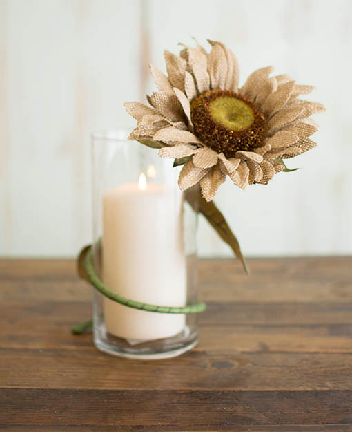 A wealth of design options available using the sturdy, bendable wire stems on our collection of burlap flowers! Shown here wrapped around a clear glass vase sheltering an ivory pillar candle, each sold separately.