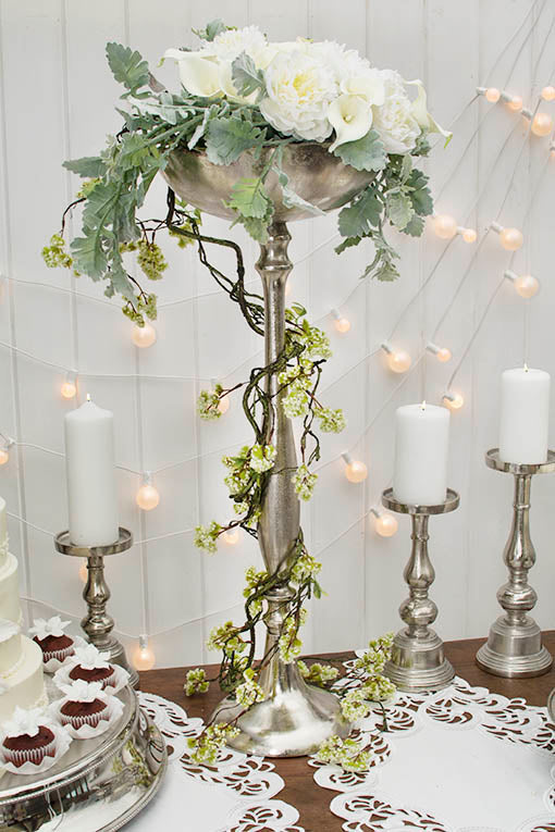 Add graceful greenery to your next event to evoke a fresh yet elegant garden style. Pictured with a variety of silver tone metallic accessories, each sold separately.