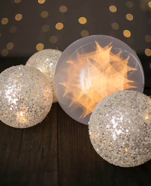 Our LED lighted orb illuminates holographic star shapes next to our sequin spheres.