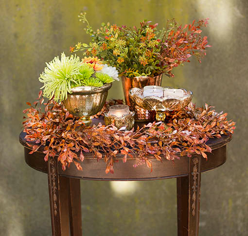 Copper and rose gold accents set a glowing table combined with gold mercury glass, sold separately.