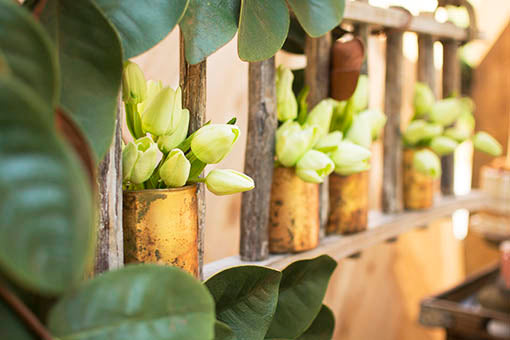 Create unique wall art by combining our tulips with mercury glass vases, a wooden ladder, magnolia garland and burlap runner.