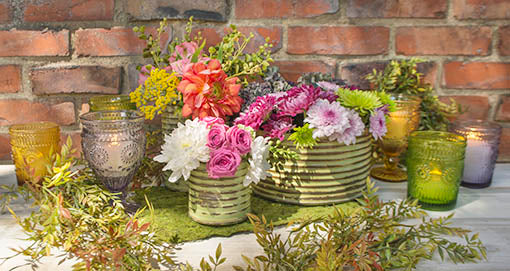 Use always vibrant moss mats as a backdrop for gorgeous floral centerpieces. Weathered tin canisters juxtapose beautifully with kaleidoscopic glassware.
