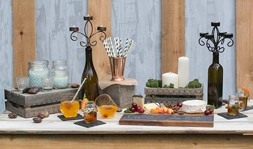Take the industrial chic route by mixing the cheese board with metals, such as our copper julep cup, and intricate designs, like the bottle candelabras.