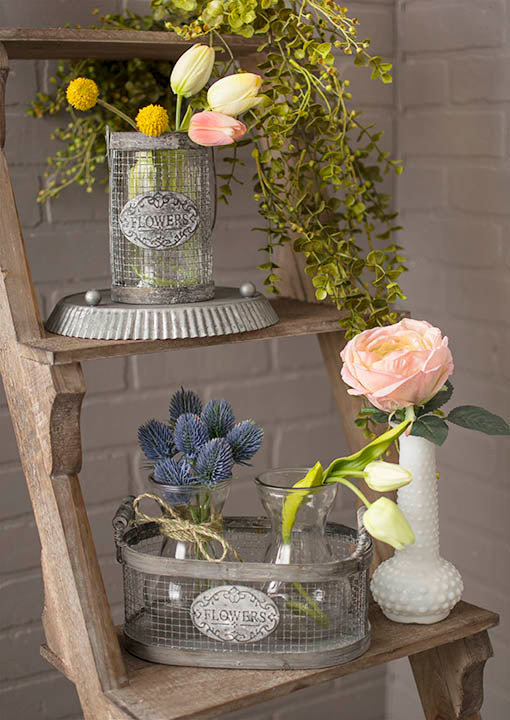 Colorful twine as a bottle accent and our corrugated tart pan used as a riser elevate decorative florals in these charming baskets. Pair with milk glass vases to complete the look.