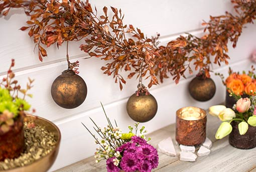 Decorate our copper swag with these spheres for a metallic design that mercury glass candle holders and soft green tulips