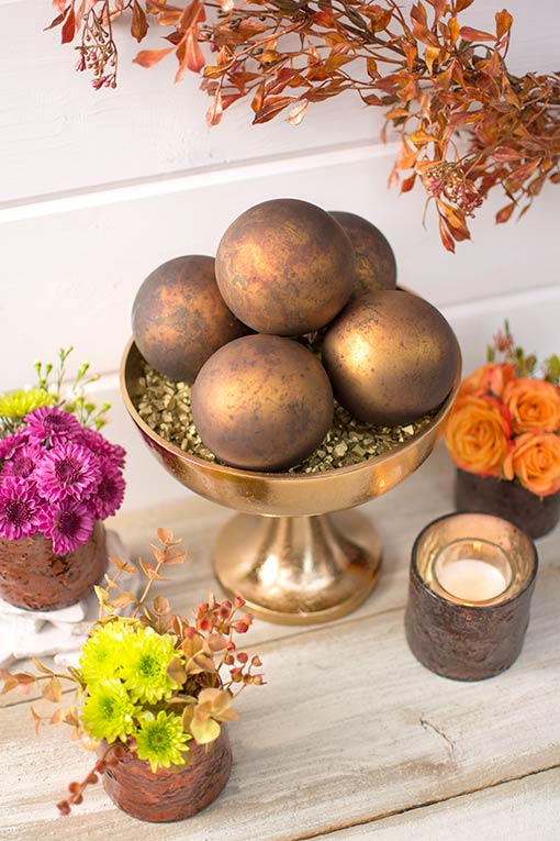 Fill a metal compote with gold toned vase filler and these ornaments to complete your luxurious wedding table design.