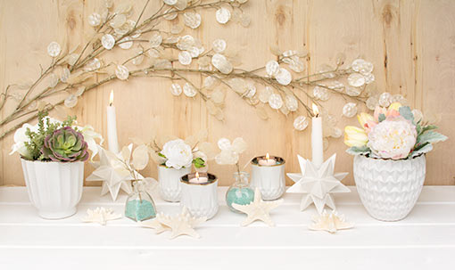 Compose a sea worthy display for your beach chic wedding by accenting your table with this sea stars. Add geometric vases and candle holders, clear glass bud vases, starburst candle holders and a silver dollar spray.