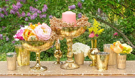 Glitter your tables in gold at your wedding or event. The compotes complement our set of candle holders and carved bud vases. Finish the scene with flowers and berry branches..