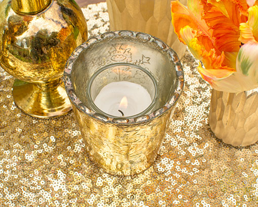 Place a votive candle in this scalloped edge holder on a sequin table runner.