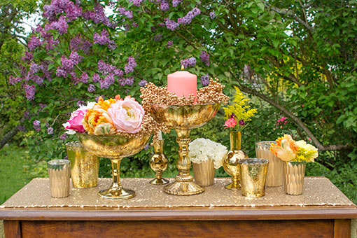 Dress your table in hues of gold from our candle holders and compotes. Add our carved bud vases, a sequin table runner, gold toned berries and a bright selection of flowers to complete this dramatic design.